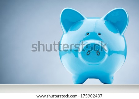 Front closeup image of a blue piggy bank with copy space. - stock photo