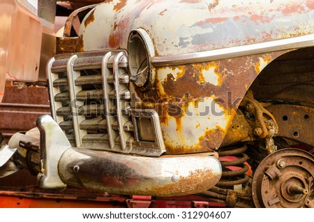Front corner of a wrecked vintage car in a wrecking yard - stock photo