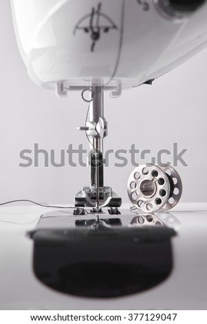 Front detail sewing machine needle and thread spool. Vertical composition. Front view close up - stock photo