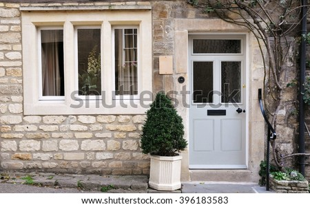 Front Door and Exterior of a Beautiful Old English Stone Cottage - stock photo