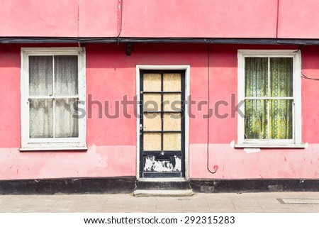 Front door and external wall of a traditional pink cottage in the UK - stock photo