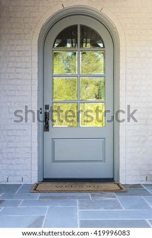 Front door, close up view an arched door with reflection  - stock photo
