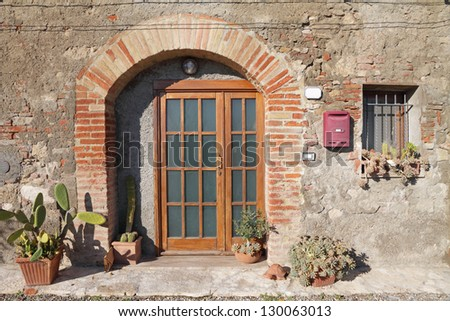front door decorated with cactus plants in tuscan village, Italy, Europe - stock photo