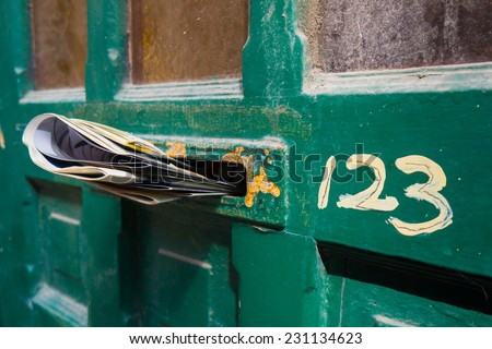 Front door letter slot full of newspapers - stock photo