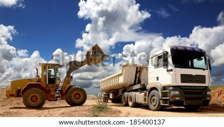 Front end loader placing stone and sand into a large truck or trailer - stock photo