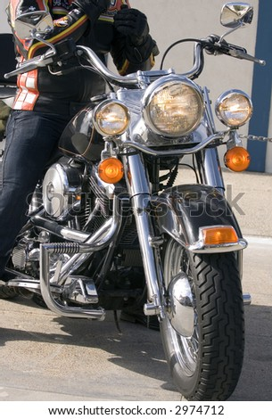 Front end of motorbicycle with rider - stock photo