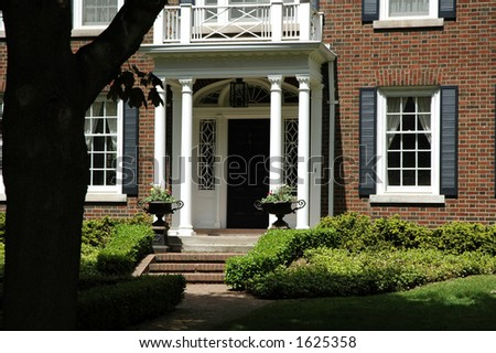 Front entrance of luxury house with pretty iron flower urns - stock photo