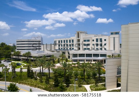 Front entrance to a hospital with palm tree landscaping and blue sky - stock photo