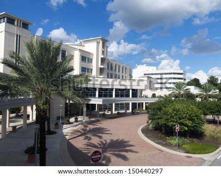 Front entrance to a modern hospital with palm tree landscaping and blue sky - stock photo