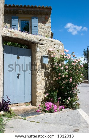 Front entrance to a small but charming French village home. I love the bits of colored glass protruding from the cement along the ledge. - stock photo