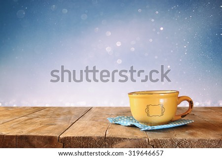 front image of coffee cup over wooden table in front of glitter background - stock photo