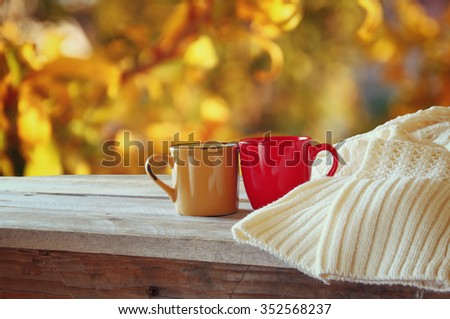 front image of two coffee cups over wooden table and woolen sweater  in front of autumnal sunset background. Valentines Day concept  - stock photo