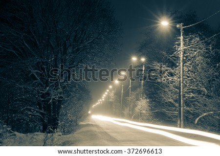 Front lights of car on snowy road by winter night, long exposure toning image - stock photo
