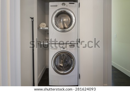 Front load washer and dryer with open closet and towels. Great design idea when there is no laundry room. - stock photo