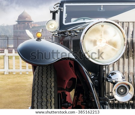 Front low angle view of oldtimer vintage saloon car. The front lights and chrome grill of classic beauty looking solid yet elegant and attractive. - stock photo