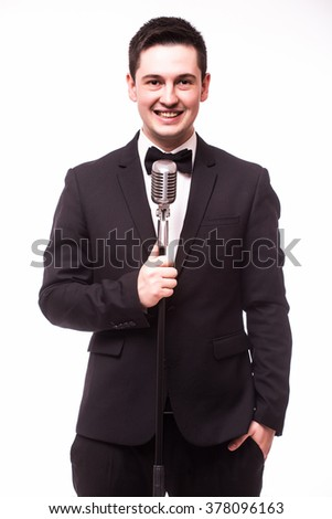 Front-man in suit singing with the microphone and smile. Isolated on white background. Showman concept. - stock photo