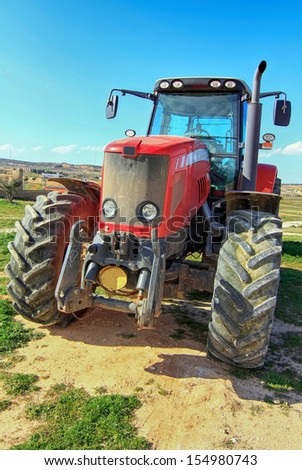 front of a modern red tractor - stock photo