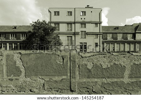 Front of abandoned wall and building. Sepia version. - stock photo