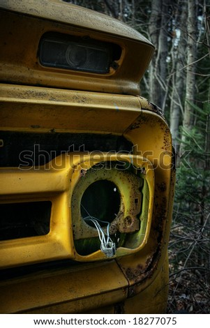 Front of an old school bus abandoned in the forest - stock photo