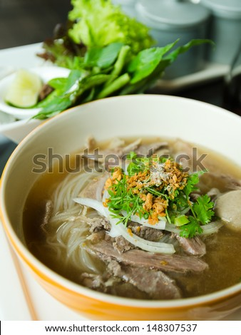 Front of Pho Lao style noodle soup with vegetables on table - stock photo