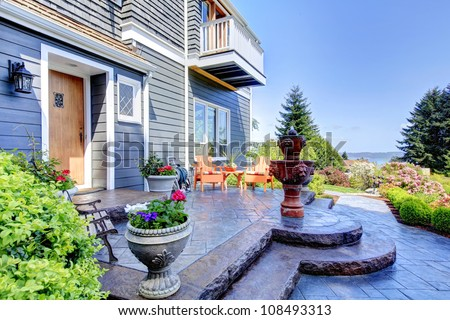 Front of the blue luxury house exterior with fountain and nice landscape. - stock photo