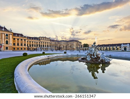 Front of the Schoenbrunn Palace in Vienna at sunset - Austria. It is a former imperial summer residence and one of the most important cultural monuments and major tourist attractions in the country. - stock photo
