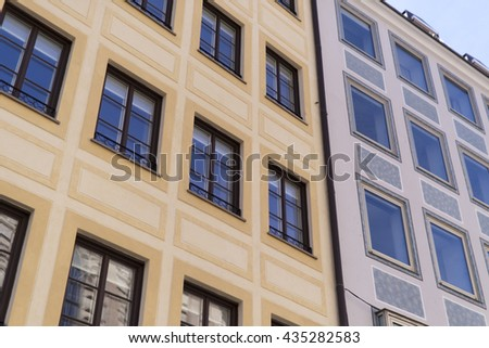 Front of traditional houses in Munich, Germany against a clear blue sky - stock photo