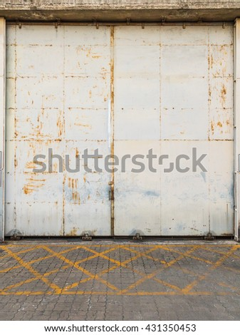 front of warehouse, dirty old metal gate, doors closed, abandoned factory. - stock photo