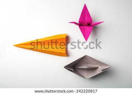 front photo of colored paper origami plane crane, boat - stock photo
