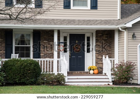 Front porch of suburban home decorate for fall holidays - stock photo