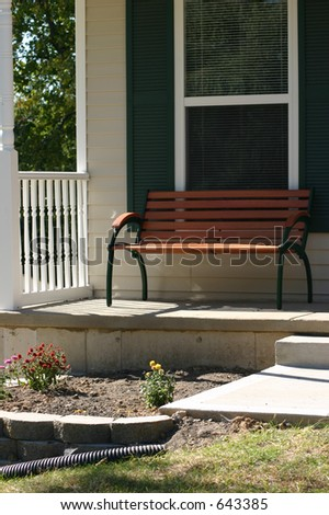Front porch with wooden bench to relax on. - stock photo