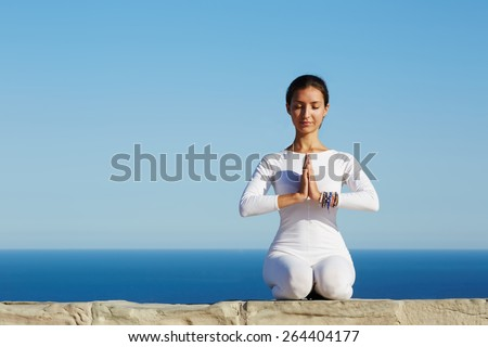 Front portrait of gorgeous young woman practicing yoga on a sunny day with amazing sea horizon on background, woman seeking enlightenment through meditation, relaxed girl performing yoga routine - stock photo