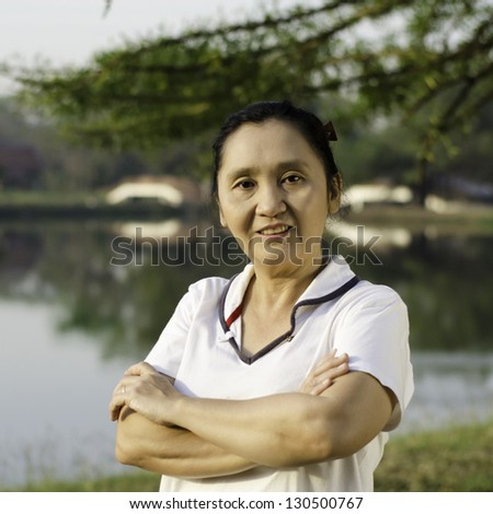 Front shot of cheerful mature woman in park outdoor - stock photo