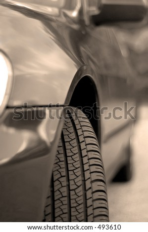 Front tire of a car with the clouds and sky reflecting in its fender paint. Black and white (sepia) - stock photo