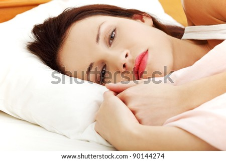 Front view face closeup of a beautiful young woman lying in bed, cuddling to the sheet and worrying. - stock photo