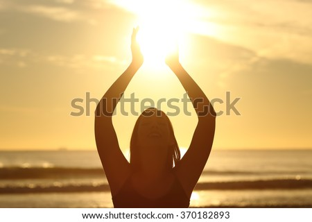 Front view of a back light of faithful woman silhouette holding sun on the beach at sunrise with a warm background - stock photo