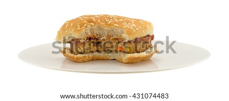 Front view of a bitten veggie burger in a bun with ketchup on an off white plate isolated on a white background.  - stock photo