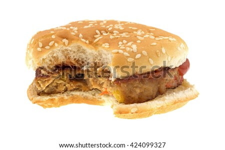 Front view of a bitten veggie burger on a bun with ketchup isolated on a white background.  - stock photo