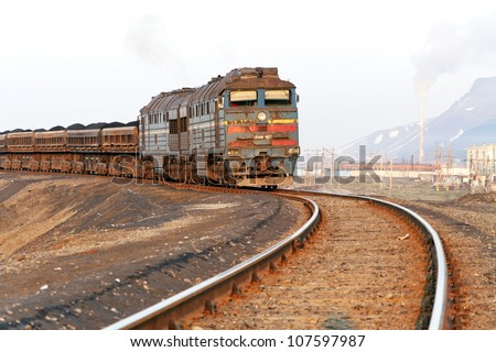 Front view of a freight train, illuminated by the setting sun. Narrowing in the future railway line. - stock photo