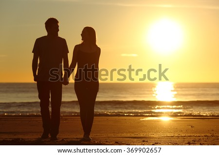 Front view of a full body of a couple silhouette walking together on the beach at sunset in summer - stock photo