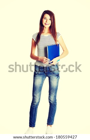 Front view of a full lenght young happy female caucasian student holding a notebook, on white. - stock photo