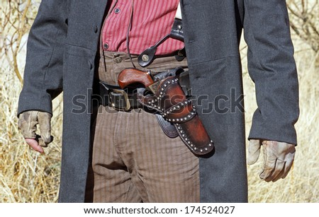 Front view of a gunfighter ready to draw his gun - stock photo