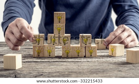 Front view of a man arranging wooden blocks with hand drawn yellow lightbulb in a random structure. Conceptual of research, education and innovation. - stock photo