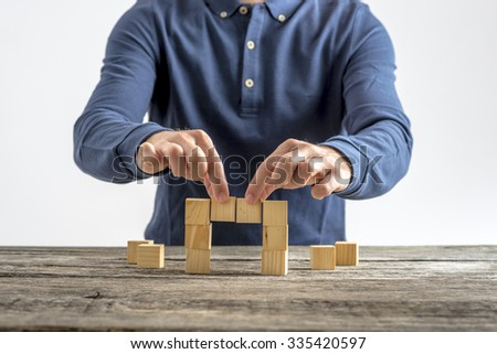 Front view of a man making a bridge with wooden cubes. Conceptual of business, education and construction. - stock photo