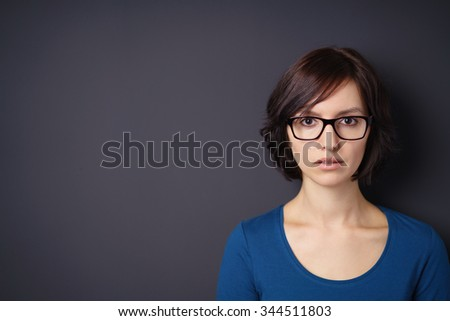 Front View of a Pretty Young Woman Wearing Eyeglasses Staring at You Against Gray Wall Background with Copy Space on the Left. - stock photo