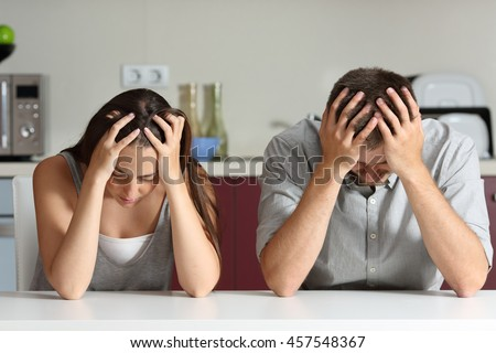 Front view of a sad couple with hands on head sitting in the kitchen of a house - stock photo