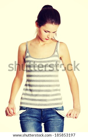 Front view of a sad young female caucasian teen taking out empty pockets - stock photo