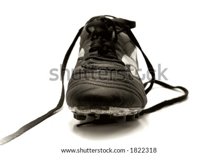 front view of a soccer shoe with dramatic lighting, studio style. Sepia-toned to create mood. - stock photo