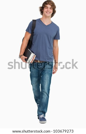 Front view of a student walking with a backpack and books against white background - stock photo