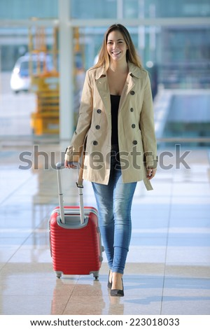 Front view of a traveler woman walking carrying a suitcase in an airport corridor - stock photo